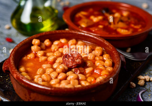 closeup of an earthenware bowl with potaje de garbanzos, a chickpeas stew with chorizo and serrano ham, and a bowl - Stock Image