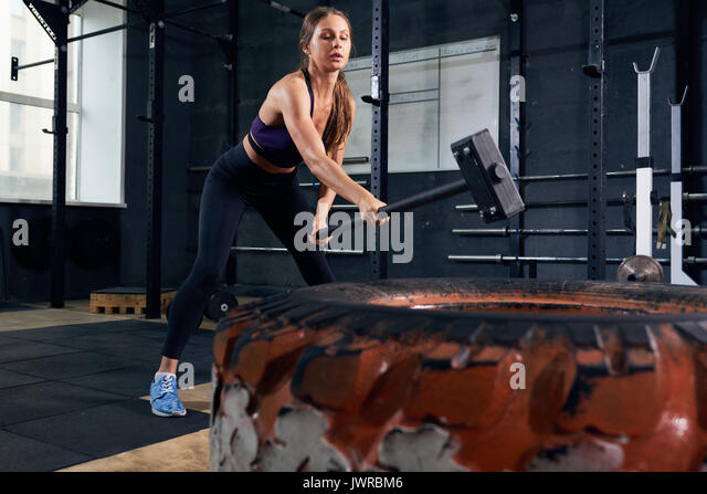 Portrait of strong young woman smashing large tire with sledgehammer during crossfit workout in modern gym - Stock Image