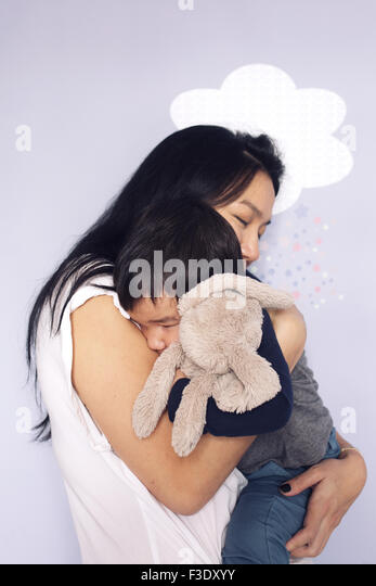 Mother embracing young son - Stock Image