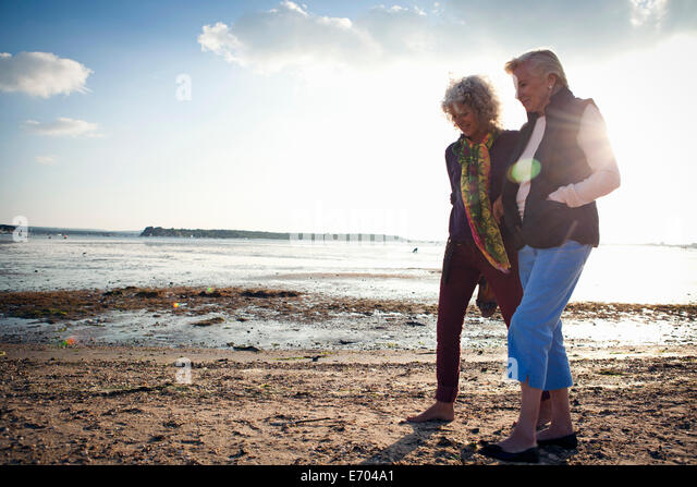 Mother and daughter walking on beach - Stock Image