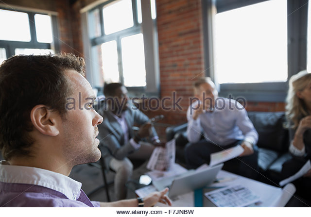 Business people looking away in meeting - Stock Image