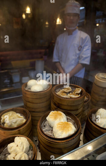 A cook steaming dim sum in bamboo steamers at an eatery in China. - Stock Image