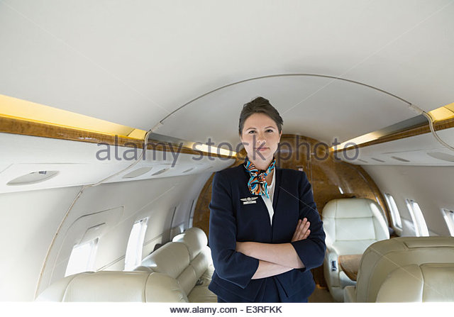 Portrait of confident flight attendant on corporate jet - Stock Image