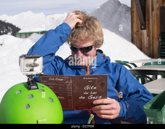 Man thinking scratching his head whilst trying to decide what to eat from a menu outside Gite du Lac de Gers ski - Stock Image