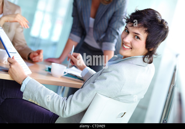Portrait of a cheerful business girl distracted in the process of discussion - Stock Image