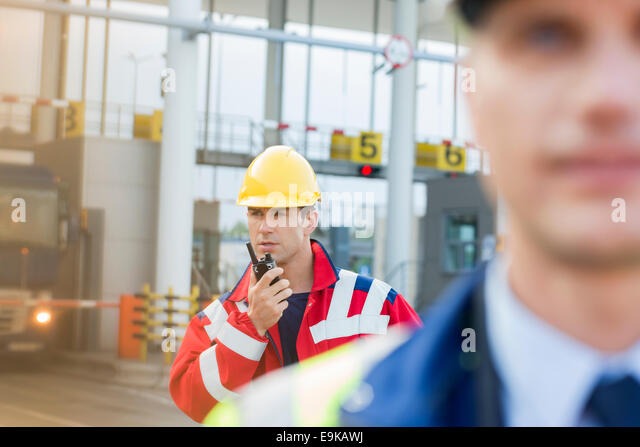 Male worker using walkie-talkie with colleague in foreground at shipyard - Stock Image