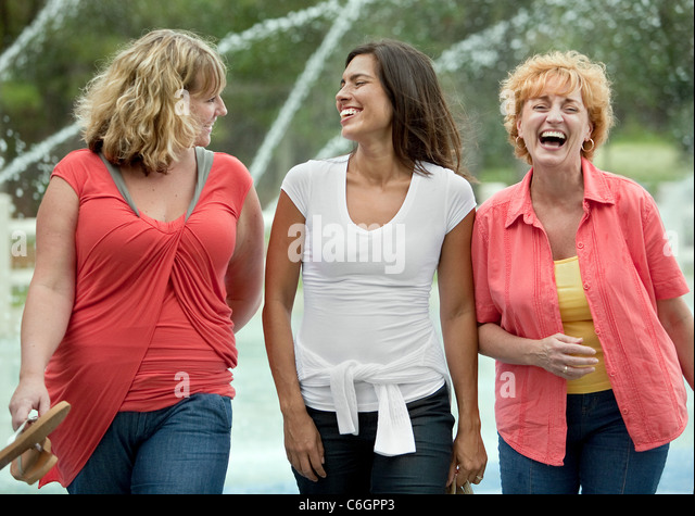Three women enjoy themselves at a local park while taking a walk to promote an active healthy lifestyle. - Stock Image