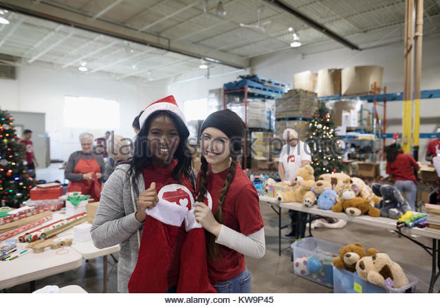 Portrait smiling,confident young female volunteers filling Christmas stockings in warehouse - Stock Image
