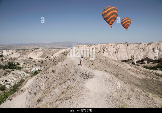 Female tourist and hot air balloons in rock formation landscape, Cappadocia, Anatolia, Turkey - Stock Image