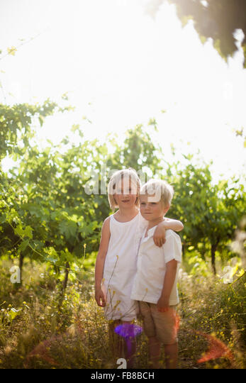 Italy, Tuscany, Portrait of sister (6-7) embracing younger brother (4-5) in orchard - Stock Image