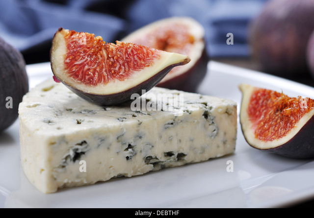 blue cheese and sweet fruit figs on a white plate - Stock Image