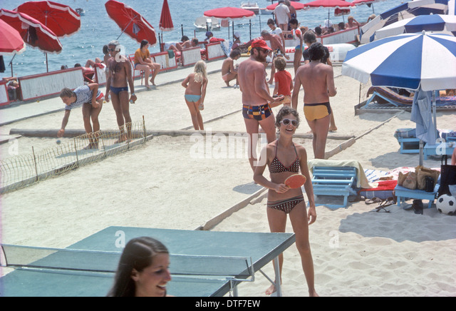 Table tennis in bathing suits South of France. Leisure seaside umbrellas sunshine - Stock Image