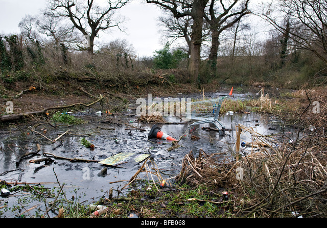 Rubbish thats been dumped on a frozen local duck pond by hooligans - Stock Image