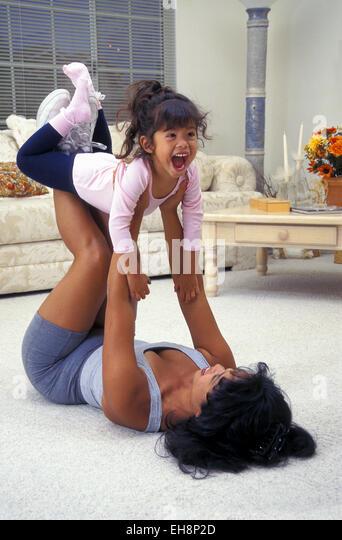 Filipina mom exercising on floor lifts her laughing pre-K daughter with her legs.  MR © Myrleen Pearson - Stock-Bilder