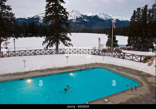 Woman alone swimming in outdoor swimming pool wiht snow and mountains in the background, Jasper Park Lodge, Canada - Stock Image