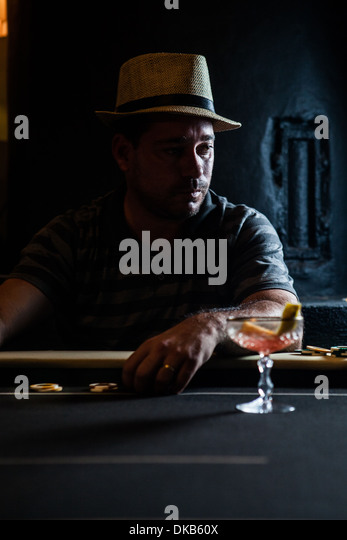 Mid adult man sitting at table with gambling chips and cocktail - Stock Image