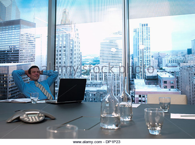 Smiling businessman with hands behind head in conference room - Stock-Bilder