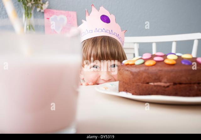 Girl hiding behind cake - Stock Image