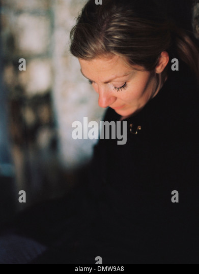A woman wearing a black coat looking down in a pensive mood. - Stock Image