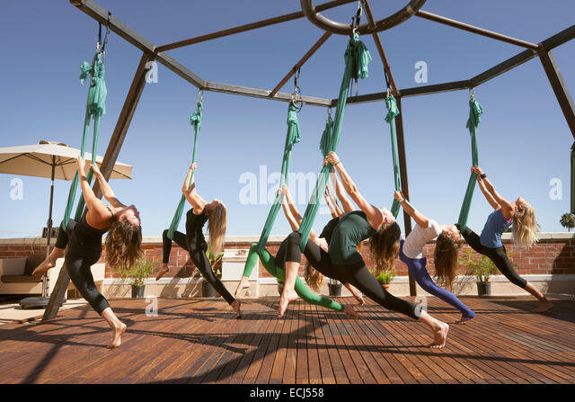A group performs aerial yoga. - Stock Image