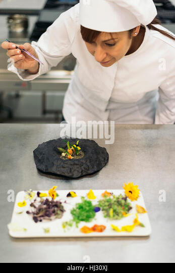 Pretty professional chef cooking in a kitchen.Cooking concept. - Stock Image