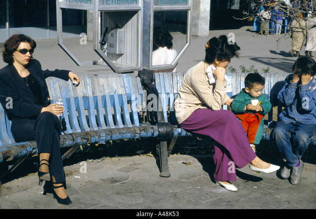 People sitting on park bences and enjoying the sun in Almaty Khazakstan - Stock Image