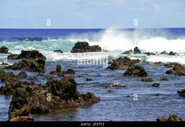 The blue sky reflects in the beautiful blue of the Pacific Ocean near the shore of Easter Island (Rapa Nui), Chile - Stock Image
