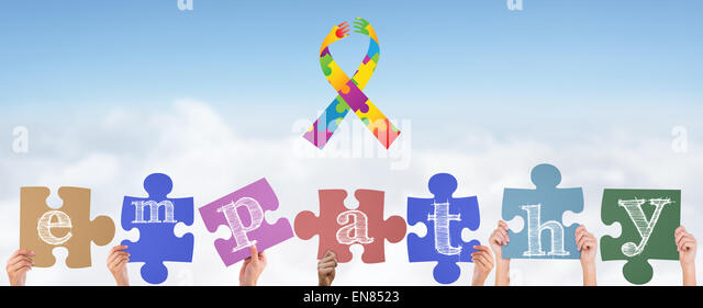 Composite image of hands holding up empathy jigsaw pieces - Stock Image