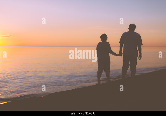 Senior couple walking along the beach - Stock Image