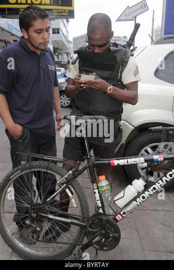 Panama City Panama Bella Vista Via Espana bicycle patrol police policeman writing ticket Black Hispanic man public - Stock Image
