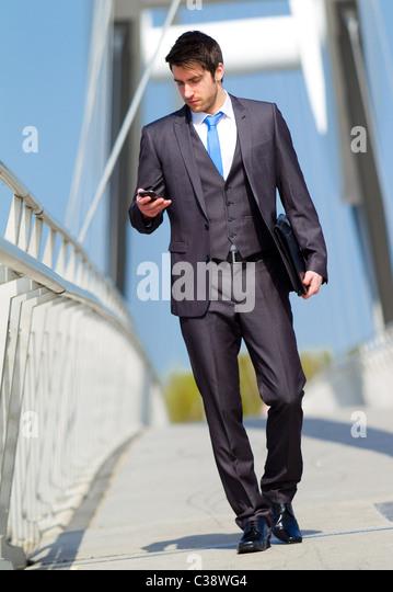Man walking looking at phone - Stock Image