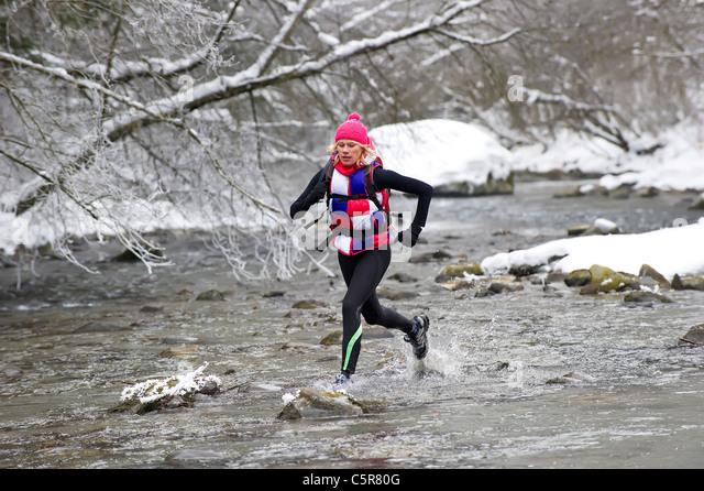 A jogger crossing a winter snowy river. - Stock-Bilder