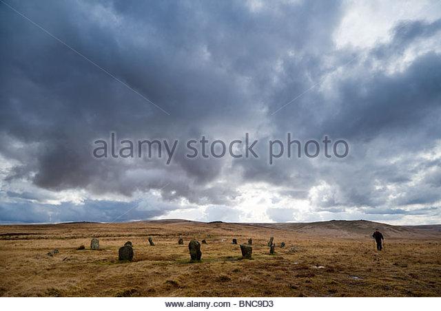 Walking past the stone circle on Cosdon Hill, North Dartmoor, Devon. - Stock Image