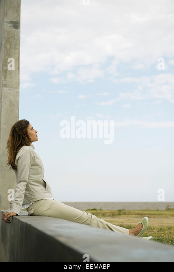 Woman sitting on a ledge looking at view, daydreaming - Stock Image