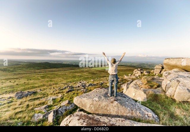 Vintage woman standing on top of hill with arms outstreched and looking at view - Stock Image