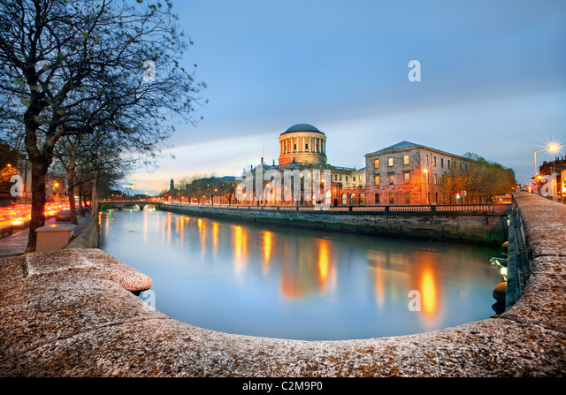 A view along the river Liffey Dublin at dusk with the Four Courts featuring prominently - Stock Image