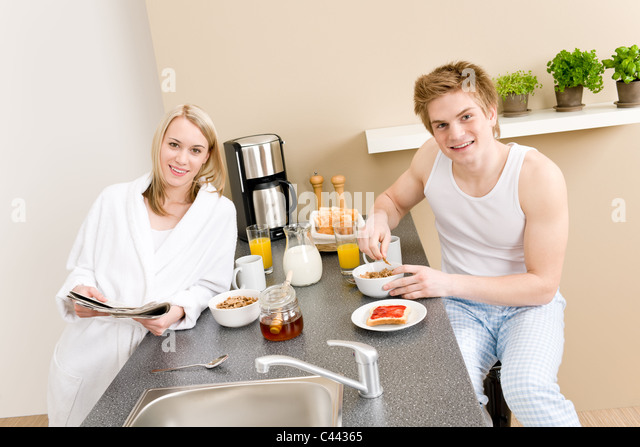 Breakfast happy couple eat cereal drink coffee in kitchen - Stock-Bilder