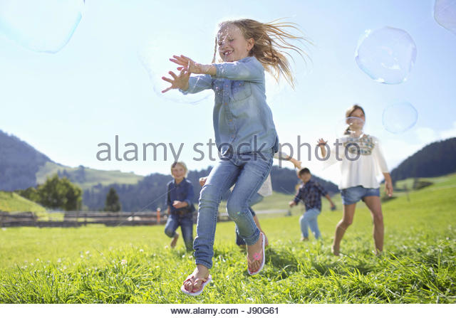 Children Chasing Giant Bubbles In Countryside - Stock-Bilder
