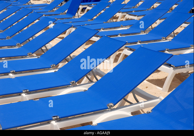 Tropics tropical beach blue louge chairs empty rows - Stock Image