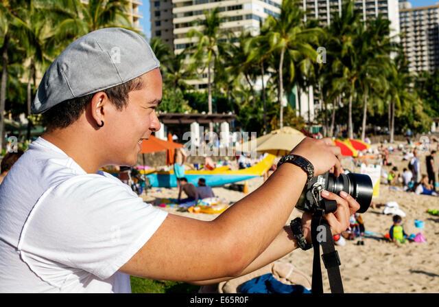 Hawaii Hawaiian Honolulu Waikiki Beach resort Kuhio Beach State Park man student photographer taking pictures camera - Stock Image