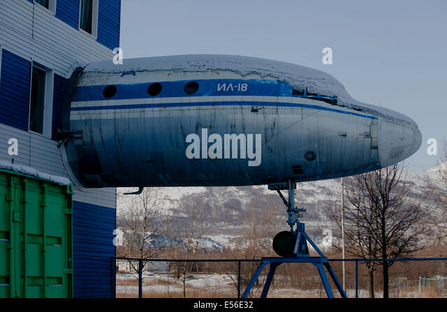 Snow covered plane fuselage sticking out building - Stock Image