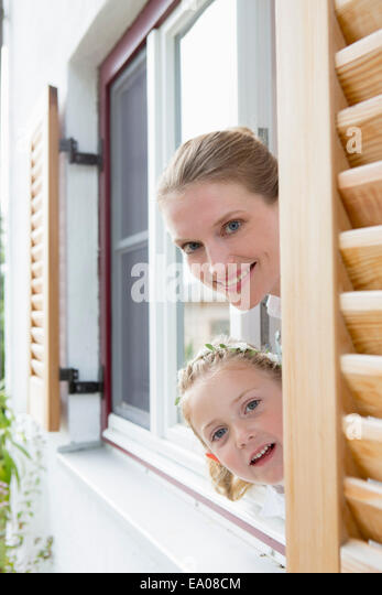 Mother and daughter peering through window - Stock Image