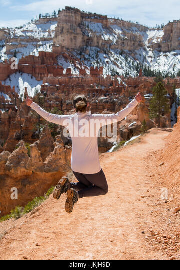 Silhouette of a Woman Jumping Over Dirt Trail with snowy Bryce in background - Stock Image