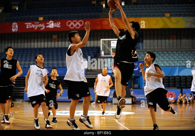 Chinese children play basketball in Beijing, China. - Stock Image