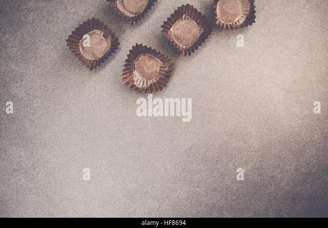 brown paper empty mini cupcake liners top view - dark slate worktop - Stock Image