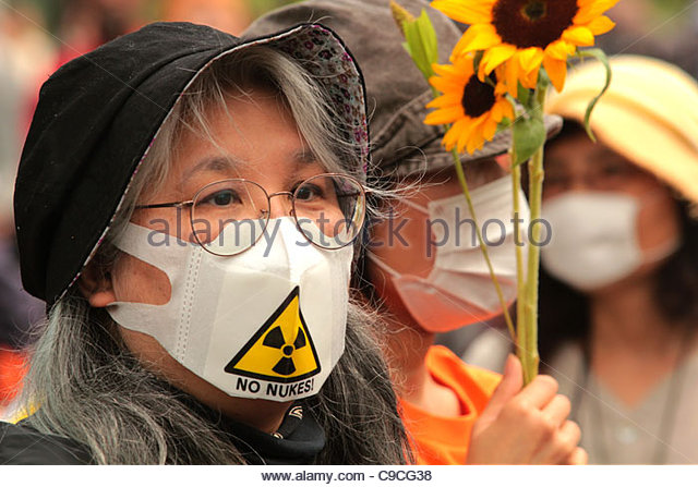 A protester wearing a No Nukes mask carries a sunflower in Shibuya, Tokyo, during an 'Energy Shift' march. - Stock Image