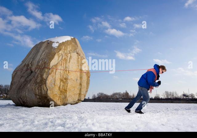 Man pulling boulder - Stock Image