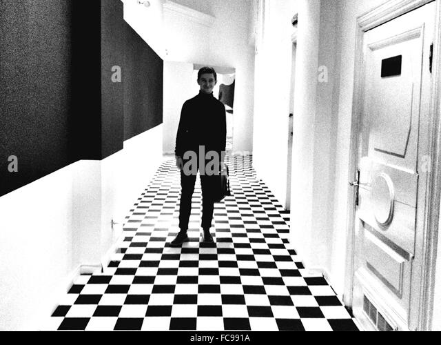 Full Length Of Smiling Man Standing In Corridor - Stock Image