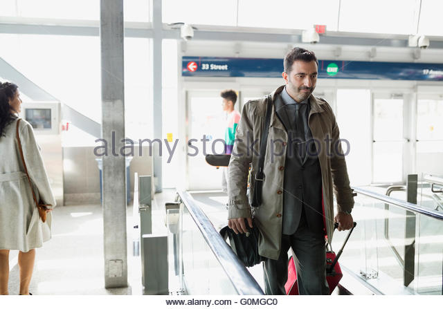 Businessman with suitcase stepping onto escalator train station - Stock Image