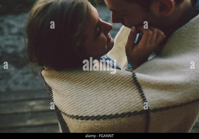 Young couple wrapped in plaid - Stock Image